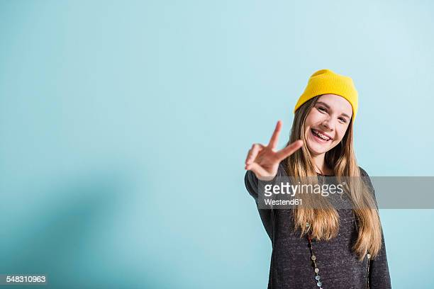 Laughing female teenager showing victory-sign wearing yellow cap