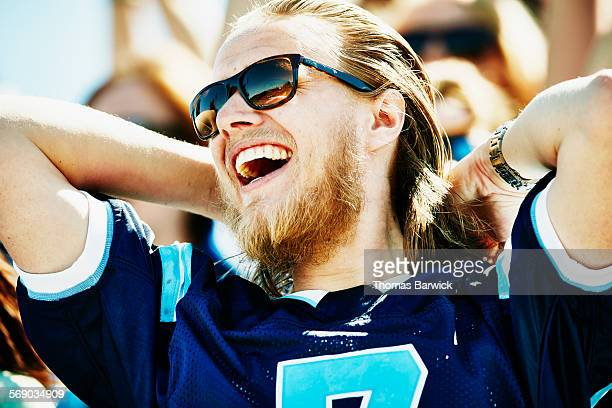 Laughing football fan celebrating in stadium