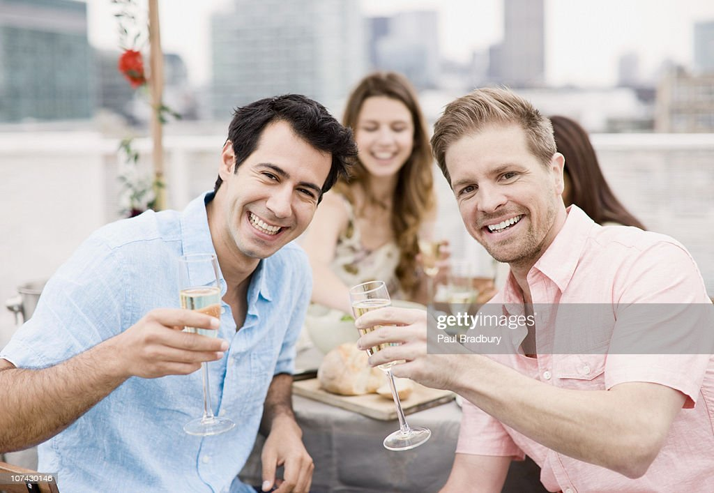 Laughing friends drinking Champagne at outdoor party : Stock Photo