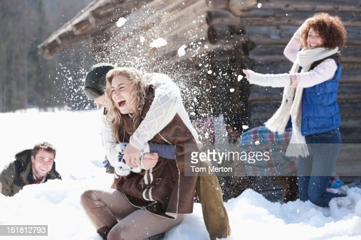 Laughing friends enjoying snowball fight