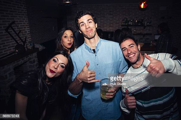Laughing friends giving thumbs up in nightclub