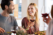Portrait of a happy friends reunion. Young couples enjoying wine and drinks. Couple enjoying lunch with family at home.