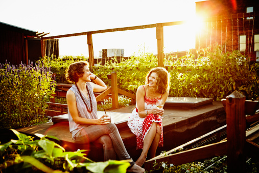 Laughing friends having drinks in garden at sunset