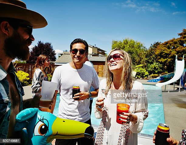 Laughing friends having drinks poolside at party