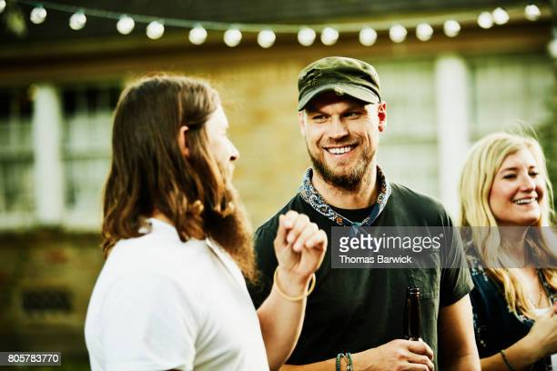Laughing friends in discussion during summertime backyard party