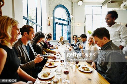 Laughing friends in restaurant eating dessert