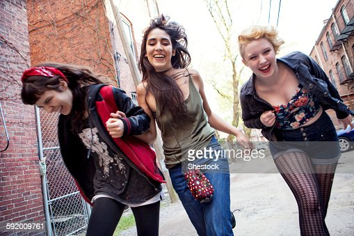 Laughing friends playing on city sidewalk