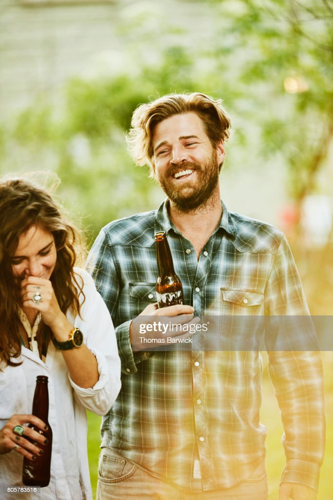 Laughing friends sharing drinks during backyard party on summer evening : Stock Photo