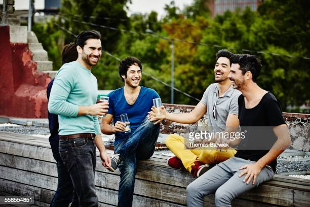 Laughing friends sharing drinks on deck