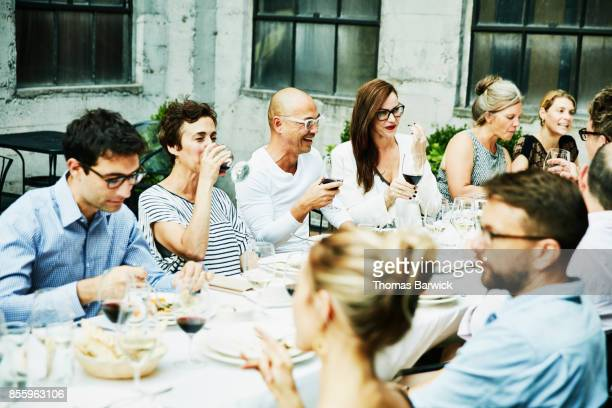 Laughing friends sharing family style meal on restaurant patio