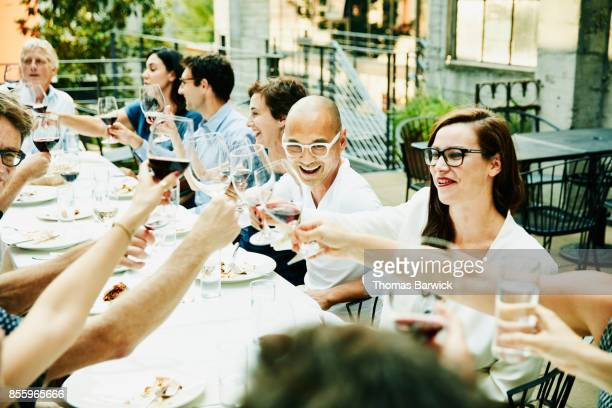 Laughing friends toasting during celebration dinner on restaurant patio on summer evening