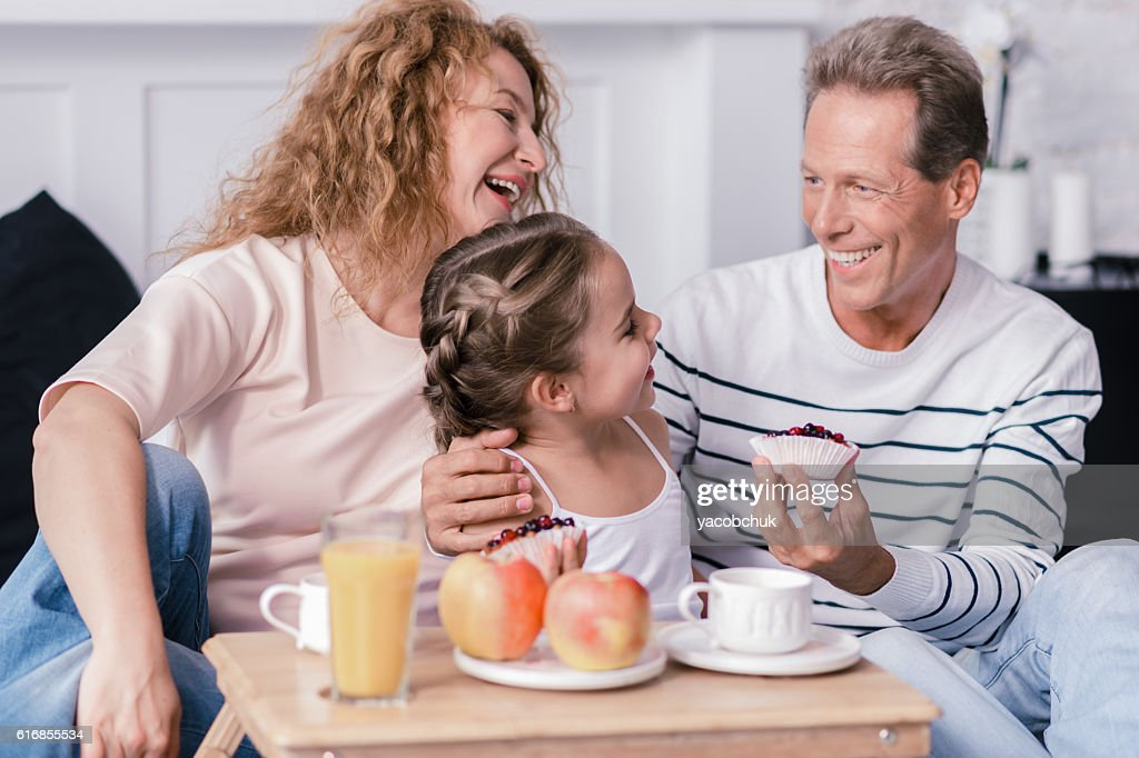 Laughing girl holding berry cupcakes with her grandparents : Stock Photo