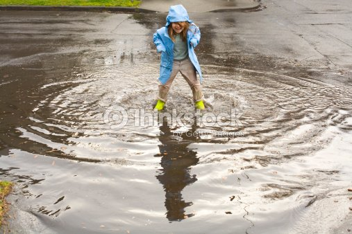 Laughing Girl Jumping in Deep Puddle : Stock Photo