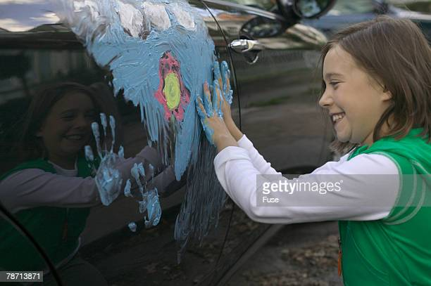 Laughing girl painting car with finger paint