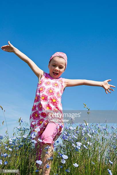 Laughing girl running across a flower meadow