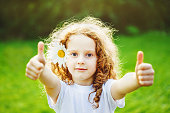 Cute little girl with daisy in her hairs, showing thumbs up in sunset light.