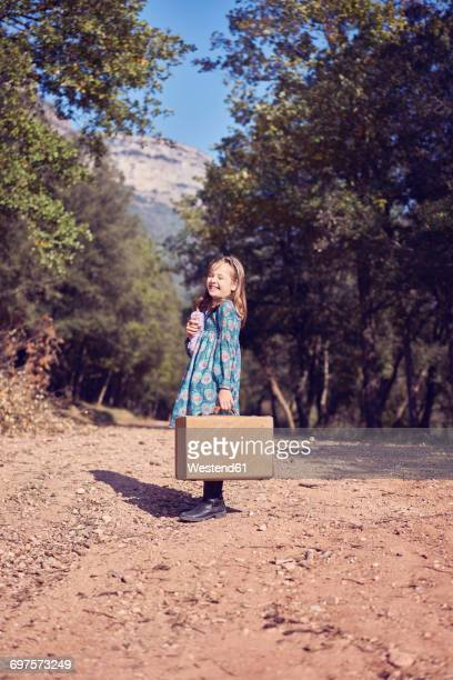 Laughing girl with a vintage suitcase