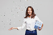 Beautiful woman with confetti and gift box at party on gray background