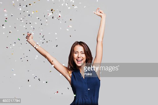 Laughing girl with falling confetti at party : Photo