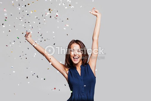 Laughing girl with falling confetti at party : Foto de stock