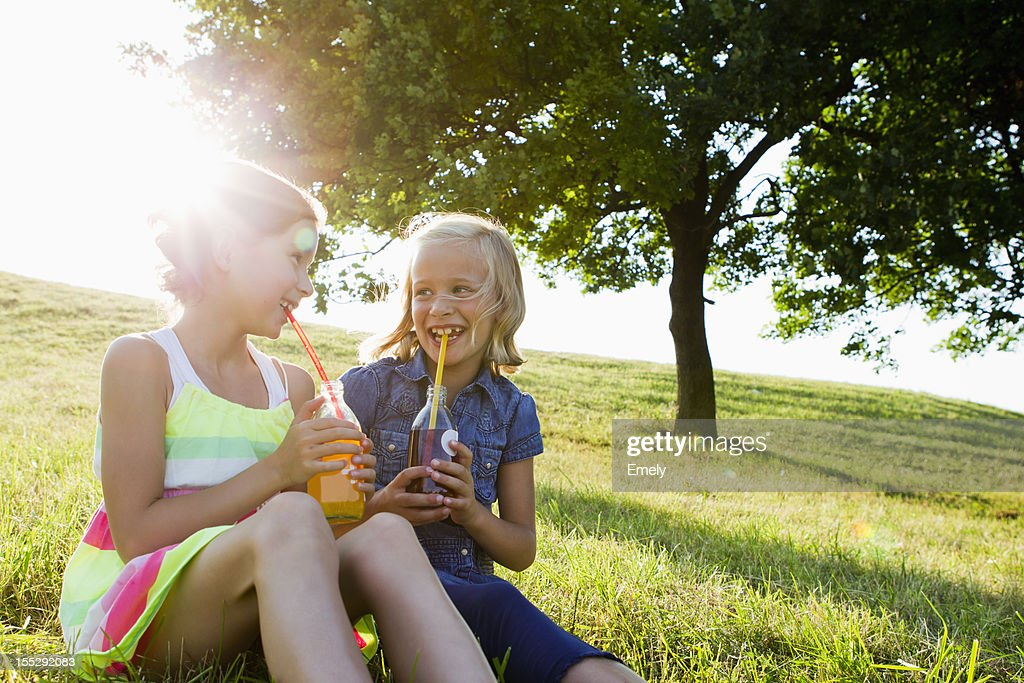 Laughing girls drinking juice outdoors : Stock Photo