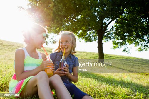 Laughing girls drinking juice outdoors : Stock Photo