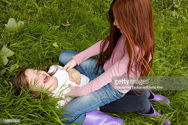 Laughing girls playing in grassy field