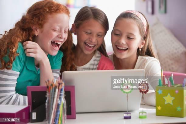 Laughing girls using laptop together