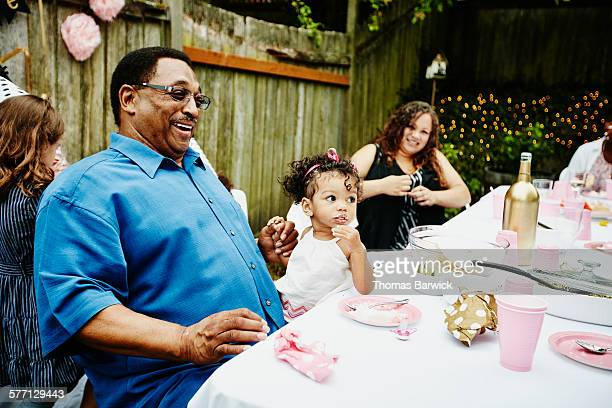 Laughing grandfather sitting with family