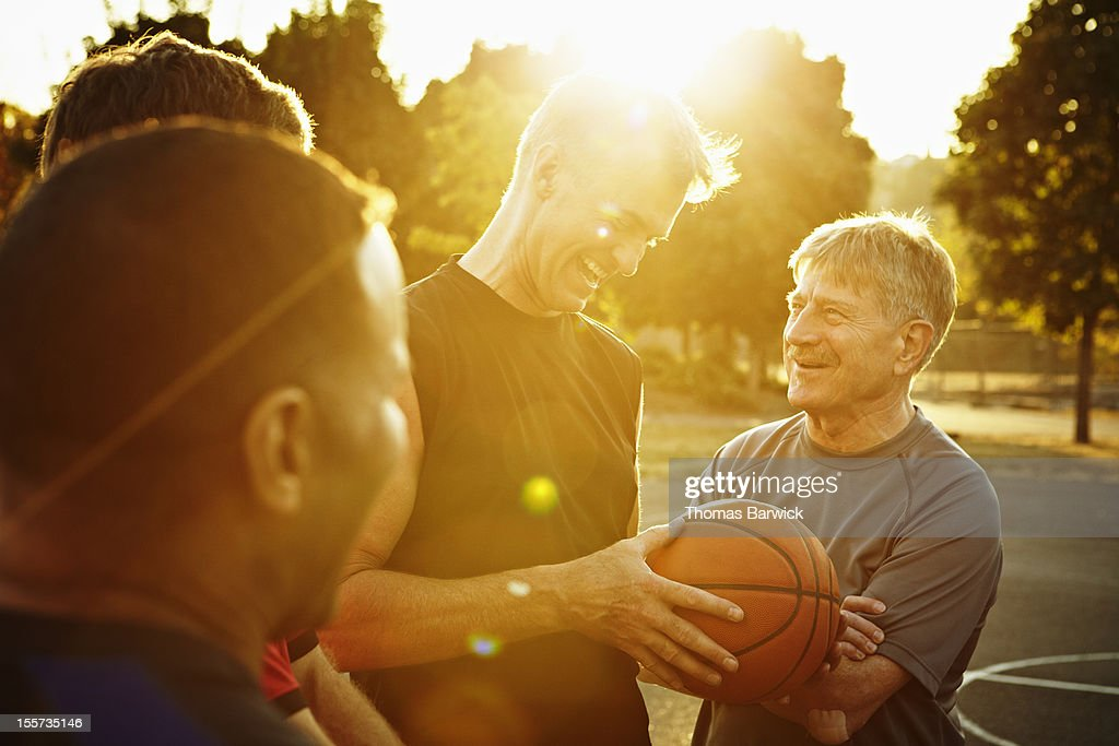 Laughing group of basketball players on court : Stockfoto