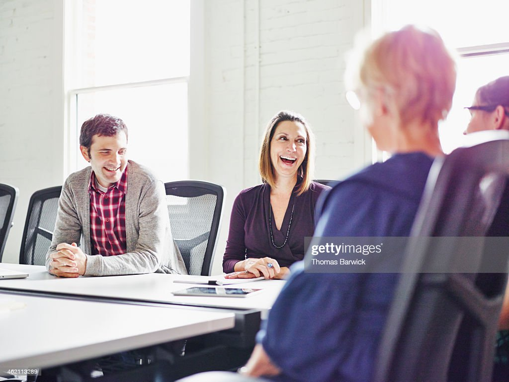 Laughing group of coworkers in conference room : Stock Photo