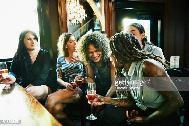 Laughing group of female friends hanging out in bar