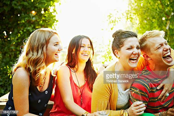 Laughing group of friends at party in backyard