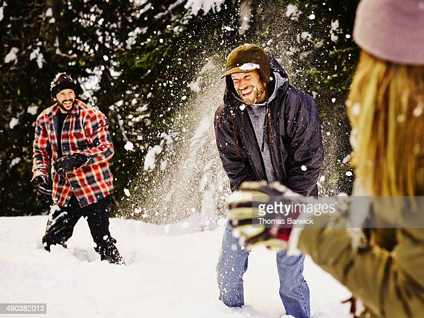 Laughing group of friends having snowball fight