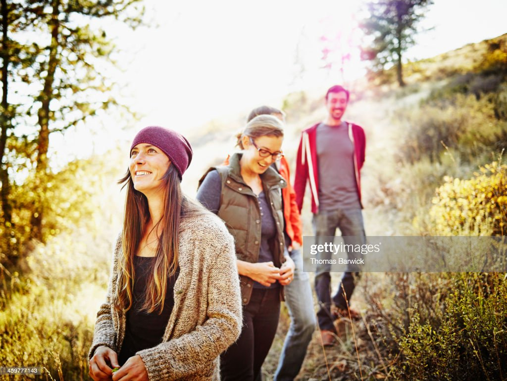 Laughing group of friends hiking on hillside