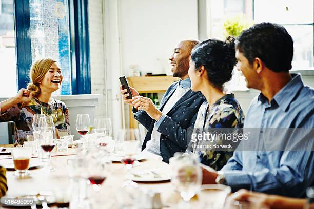 Laughing group of friends looking at smartphone