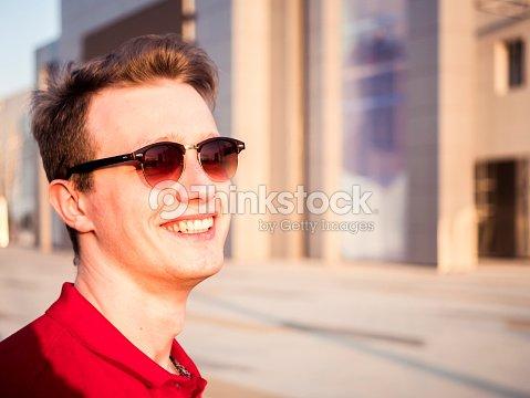 b0c1550b270557 portrait de jeune homme portant des lunettes de soleil et de la chemise  rouge en riant