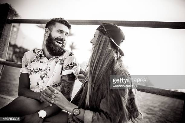 Laughing hipster guy at beach with his retro style girlfrien