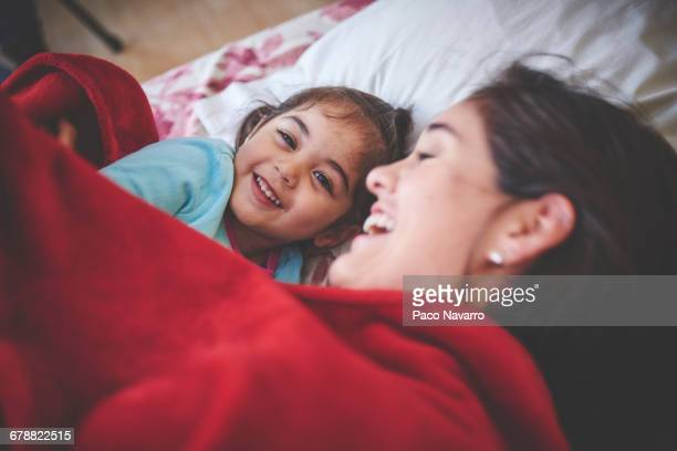 Laughing Hispanic mother and daughter under red blanket in bed