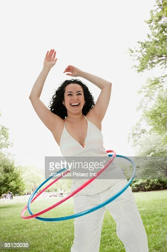 Laughing Hispanic woman playing with plastic hoops