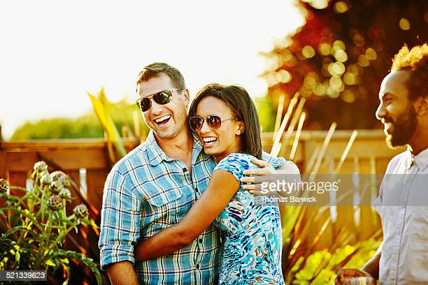 Laughing husband and wife embracing during party