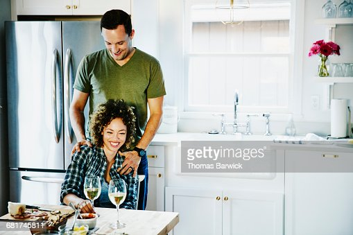 Laughing husband and wife embracing in kitchen