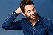 Man laughing in blue shirt, studio
