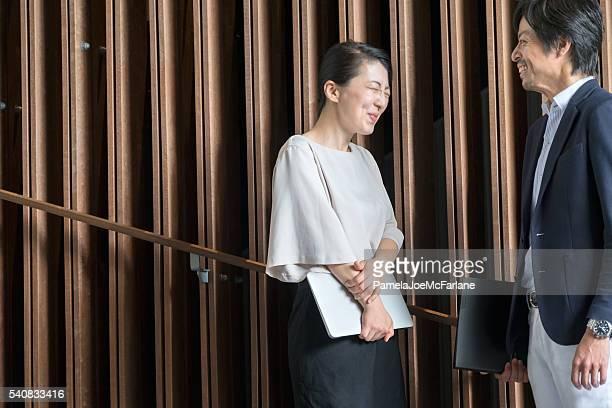 Lachen japanische Geschäftsfrau mit Laptop, Geschäftsmann mit Ordner, Büro-Lobby