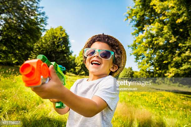 Laughing kid playing with squirt gun in park