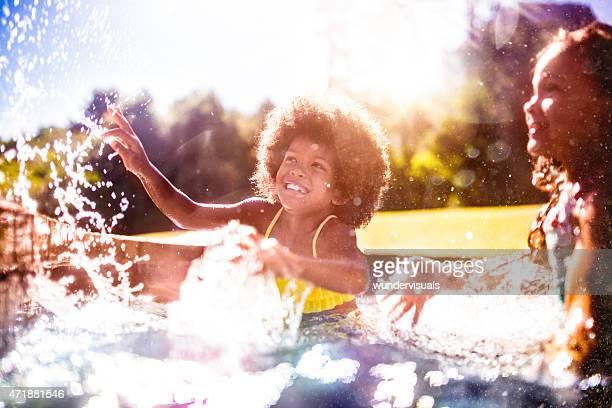 Rire petite fille Afro de plongeon avec vos amis dans une piscine