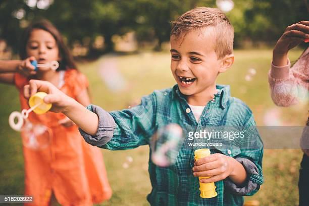 Lachend kleine Jungen spielen mit Blasen im Park