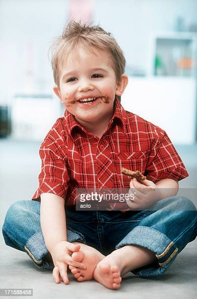 Laughing little boy with chocolate cream sandwich