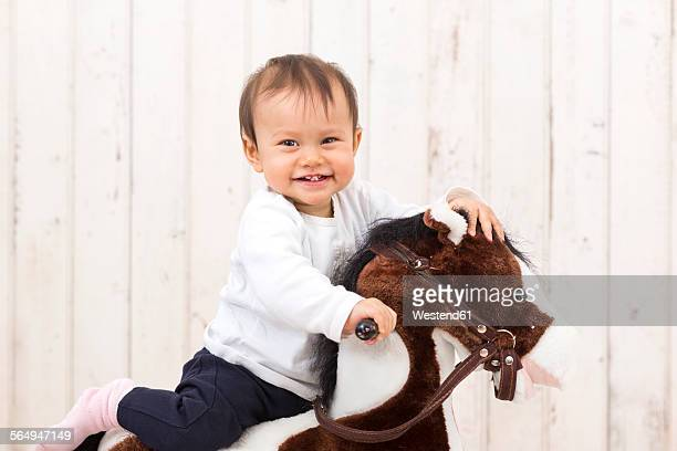 Laughing little girl sitting on rocking horse