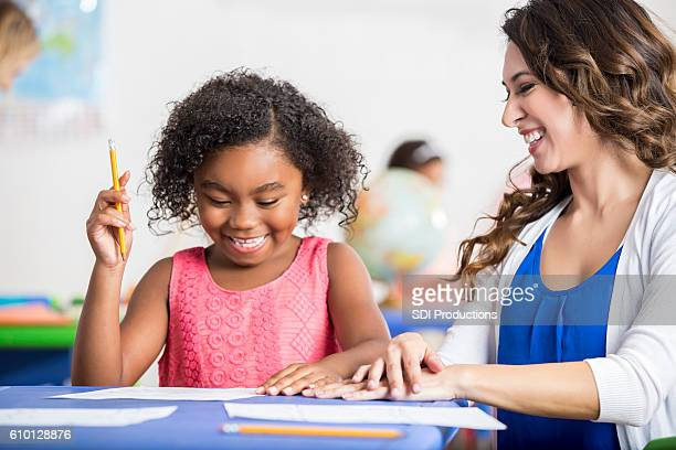 Laughing little girl working on homework with her cheerful teacher